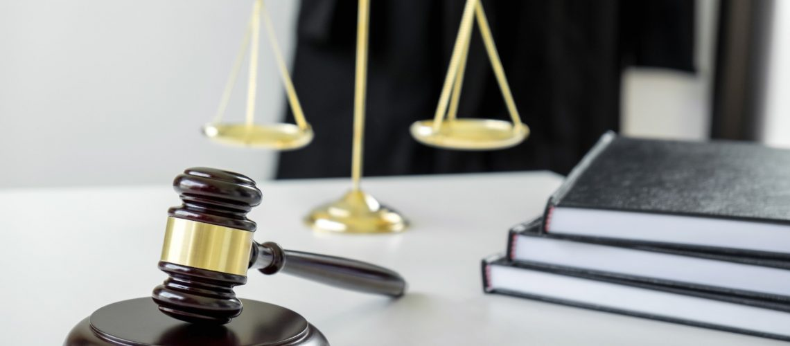 attorneys-suit-law-books-a-gavel-and-scales-of-justice-on-a-wooden-white-desktop-lawyer-and-justice_t20_6lWozO