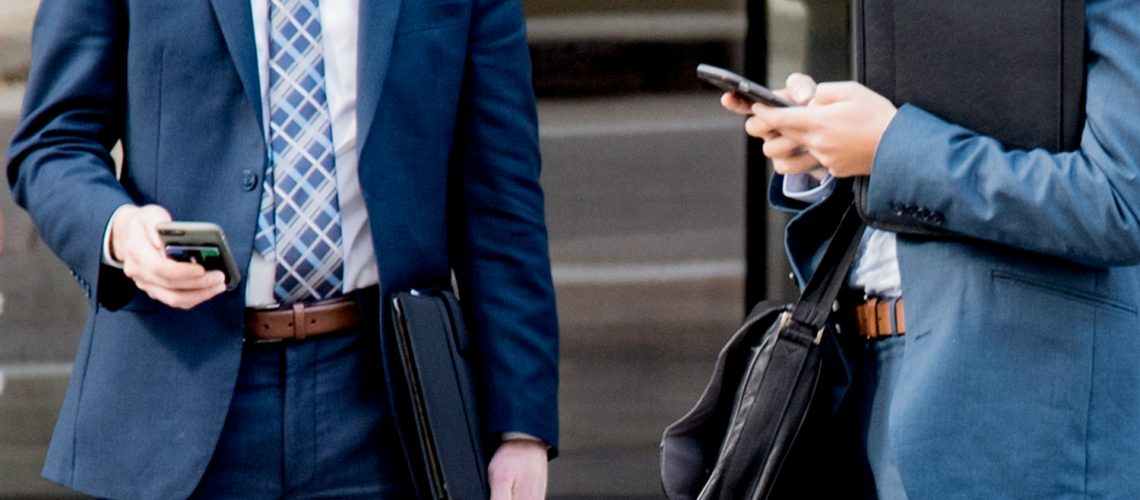 two-business-men-using-their-smart-phones-torsos-no-faces-wearing-suits-rltheis_t20_g8EVoa